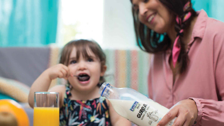 Woman pouring milk from PET bottle. Child eating.